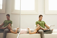 Couple relaxing together on sofa man using laptop