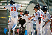 Quin Bennett leaps to land on home plate after scoring a two-run, two-out home run during the bottom of the fifth inning as his Post Falls teammates crowd the plate to congratulate him during Saturday's Little League Championship.