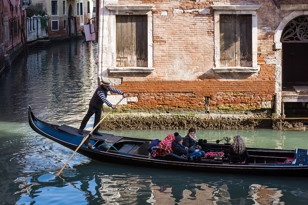 A gondolier with traditional hat is seen rowing along one of the canals in Venice Italy