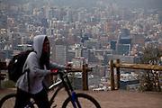 A biker passes by with Santiago's Providencia neighborhood as background.<br /> Parque metropolitano de Santiago, area verde mas importante de la capital.                      Santiago, Chile, Mayo de 2012.             Patricio Valenzuela Hohmann.