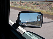 vie out the window of a classic Mini Cooper automobile with another classic Mini Cooper seen in the rearview mirror and Mt Shasta in the distance along US 97 in southern Oregon