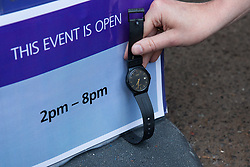 London, UK. 18 July, 2019. A climate activist from Extinction Rebellion holds a wristwatch to illustrate that Heathrow's 'masterplan' consultation event in Lambeth was closed to the public half an hour before the scheduled closing time following a peaceful non-violent die-in protest by Extinction Rebellion against plans for a third runway at Heathrow airport and to highlight Heathrow airport's major contribution to climate change.