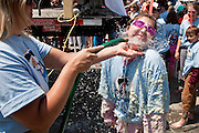 ST GEORGE, SC - APRIL 17: A young girl is hosed down after rolling around in a giant vat of grits during the World Grits Festival April 17, 2010 in St. George, South Carolina. Among the various events for the festival is the Rolling in the Grits for children where the winner is the one who can hold the most of grits to their body. Grits is corn-based porridge common in the Southern United States.   (Photo Richard Ellis)