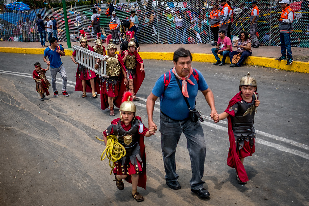 Young catholics dressed as Roman legionaries climb to the summit of Cerro de Estrella - Iztapalapa's tallest mountain. In the background the metal ladders that will be used to hang Jesus from the cross are being carried to the crucifixion site.