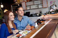 Happy young couple looking at chef serving them sushi in restaurant