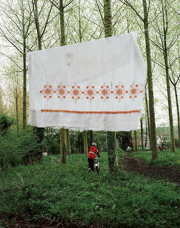 Adolescent poussant un cyclomoteur dans un sous-bois. Un torchon sèche suspendu à un fil tendu entre deux arbres,Saint-Leger-les-Domart, Picardie, France. 21.06.2002.