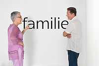 Couple discussing family issues against white wall with German text