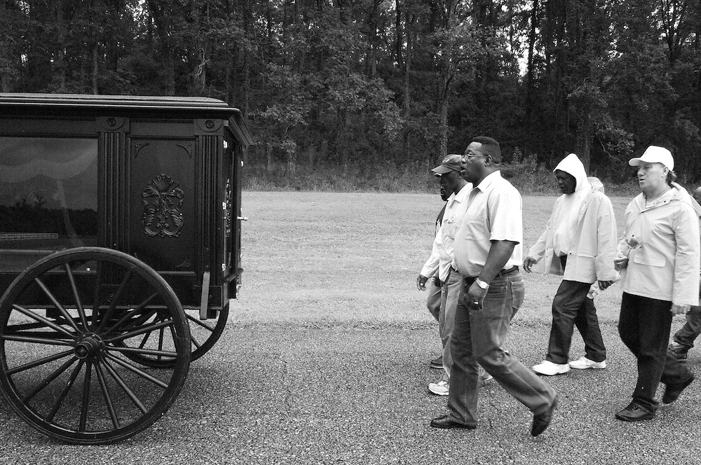 Hospice volunteers, family and friends sing hymns and walk behind the horse driven hearse carrying the body of fellow prisoner George Alexander, who died at the age of 56.  The hearse was hand built by prison carpenters at Louisiana's State Penitentiary in Angola, LA. The procession is walking to the prison's cemetary. The elaborate funerals for inmates buried in the prison's cemetary is an example of how hospice volunteers, with the support of Warden Burl Cain, have created a tone of reverence for the dying and the dead at Angola Prison.