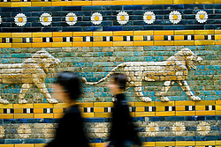 Visitors walk past ancient mosaic from Babylon at famous  Pergammon Museum in Berlin