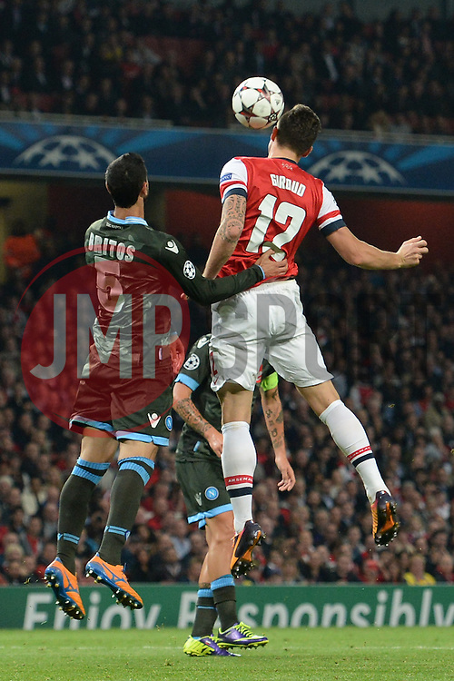 LONDON, ENGLAND - Oct 01: Napoli's defender Miguel Angel Britos from Uraguay and Arsenal's forward Olivier Giroud from France compete for the ball during the UEFA Champions League match between Arsenal from England and Napoli from Italy played at The Emirates Stadium, on October 01, 2013 in London, England. (Photo by Mitchell Gunn/ESPA)