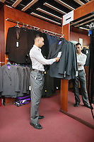Full-length of tailor standing by the clothing rack of suits