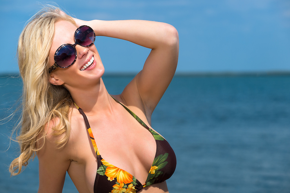 Beautiful blond woman in sunglasses and bikini relaxing and smiling while enjoying the summer sun at the seaside while on a tropical vacation