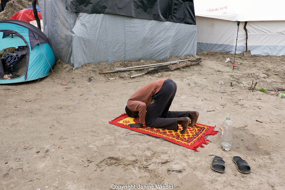 Sudanese refugee praying in The Calais Jungle Refugee and Migrant Camp in France