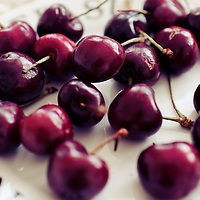 A pile of cherries with stalks.