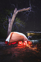A tent and jacko-lanterns in the night in the San Rafael Swell.