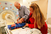 Michael Grabinski, two weeks old is immobilized in an inflatable jacket before going into a MRI machine at The Children's Hospital by his mother Calee (R) and Dr. David Brumbaugh in Aurora, Colorado August 23, 2010 during a research study on obesity in infants.  The overall theme of the study is to understand the continuum of growth that starts really at conception, and to understand if the earliest phases of growth impacts later risk for obesity.  REUTERS/Rick Wilking (UNITED STATES)