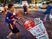 22 MARCH 2016 - BANGKOK, THAILAND:  Porters push their hand trucks through the streets around the flower market. Many of the sidewalk vendors around Pak Khlong Talat, the Bangkok flower market, closed their stalls Monday. As a part of the military government sponsored initiative to clean up Bangkok, city officials announced new rules for the sidewalk vendors that shortened their hours and changed the regulations they worked under. Some vendors said the new rules were confusing and too limiting and most vendors chose to close Monday rather than risk fines and penalties. Many hope to reopen when the situation is clarified.        PHOTO BY JACK KURTZ