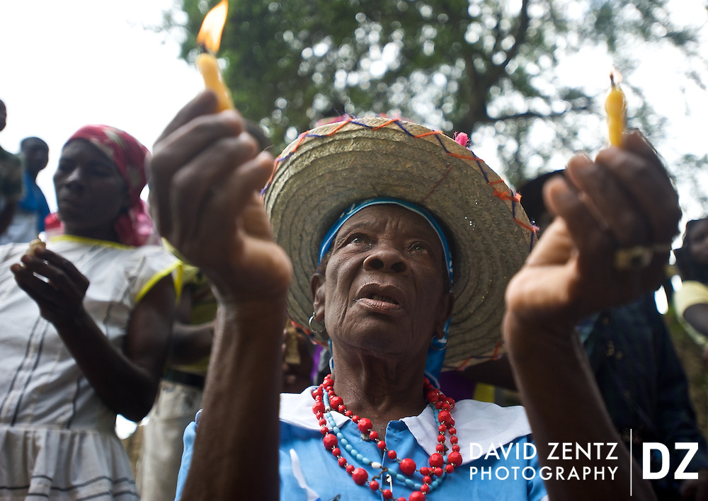 Joining other servitors, a pilgrim faces the waterfall at Saut D'eau holding lit candles to beckon and curry favor with specific lwas, or spirits on July 14, 2008. The annual festival draws Catholics and voodoo practitioners from across the country.
