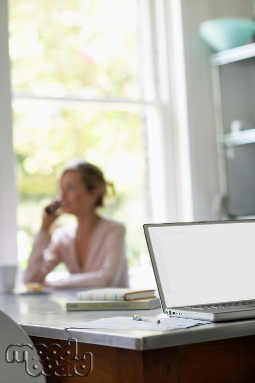 Woman on phone sitting at kitchen table by laptop focus on laptop