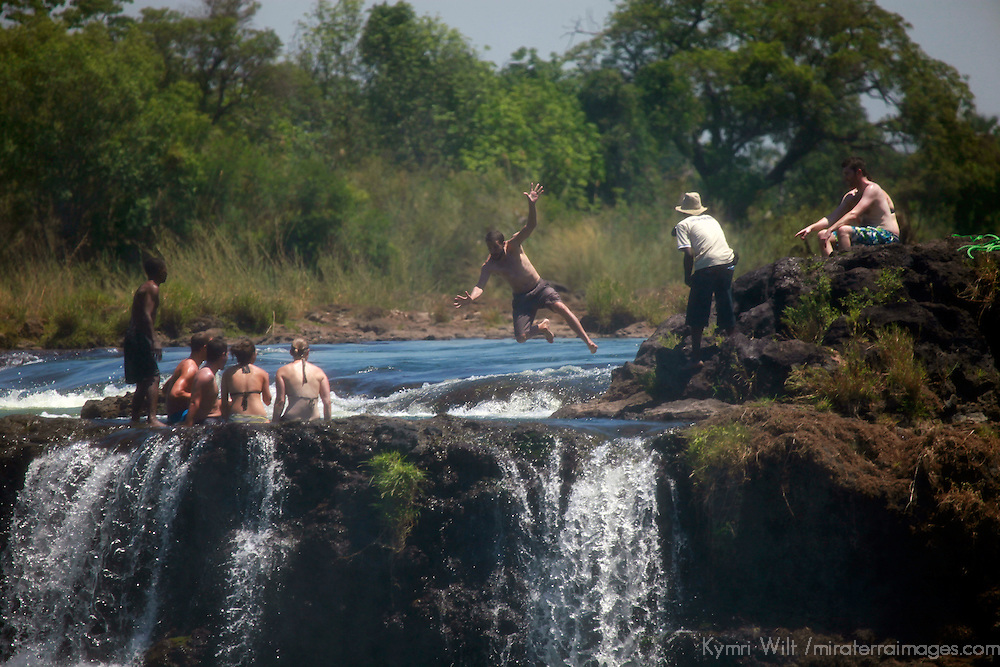 Africa, Zimbabwe, Victoria Falls. Tourists at Victoria Falls, cooling off in Devil's Pool shallows at top of falls.