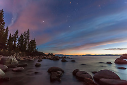"""Starry Night at Secret Cove"" - Photograph of a star filled sky with the last of the colors of sunset still visible in the clouds, shot at Secret Cove, Lake Tahoe."