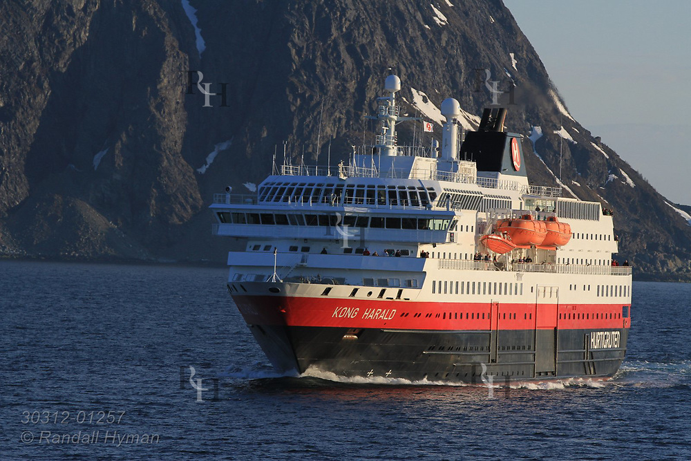 Hurtigruten cruise ship, Kong Harald, sails along snowy northern coast in late evening in mid May near Lyngen mountains, Norway.