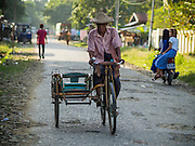 11 NOVEMBER 2014 - SITTWE, MYANMAR: A rickshaw taxi driver pedals home in the evening  in Sittwe, Myanmar. Most of the taxis in Sittwe are still pedal bike rickshaws. Most neighborhoods in Sittwe rely on well water. Sittwe is a small town in the Myanmar state of Rakhine, on the Bay of Bengal.   PHOTO BY JACK KURTZ