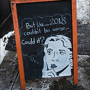 Blackboard humorous  outdoor wine store sign. Quote: &quot;But like ...2018 couldn't be worse... Could it?&quot; <br /> <br /> Sign at Terry's on Greenwich Avenue.
