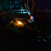 Win Jalawin sits by the fire in a local tribe member's house in the higher altitude jungle near Ban Sop Gai, Thailand.
