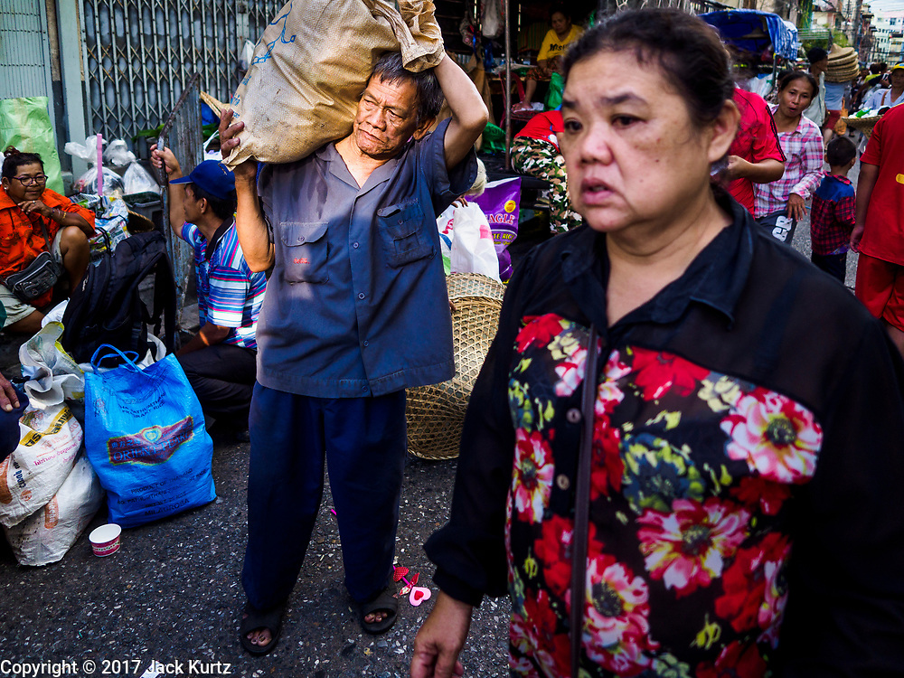 18 SEPTEMBER 2017 - BANGKOK, THAILAND: A man carries a sack of food  home after the food distribution at Poh Teck Tung on the last day Hungry Ghost Month. The Ghost Festival, also known as the Hungry Ghost Festival, Zhongyuan Festival or Yulan Festival is a traditional Buddhist and Taoist festival held in Asian countries. According to the Chinese calendar (a lunisolar calendar), the Ghost Festival is on the 15th night of the seventh month. In Chinese culture, the fifteenth day of the seventh month in the lunar calendar is called Ghost Day and the seventh month in general is regarded as the Ghost Month, in which ghosts and spirits, including those of the deceased ancestors, come out from the lower realm. Distinct from both the Qingming Festival (in spring) and Double Ninth Festival (in autumn) in which living descendants pay homage to their deceased ancestors, during Ghost Festival, the deceased are believed to visit the living.     PHOTO BY JACK KURTZ