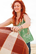 Young redhead spreads blanket out on the beach.