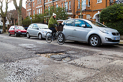 A cyclist passes a deep pothole with loose debris making Brondesbury Road's surface making it particularly dangerous to cyclists riding through West London's up-market Queens Park, as the recent cold, wet weather has given rise to the increase in potholes and road surface deterioration in London. London, March 28 2018.