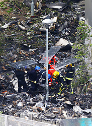 Emergency services survey the damage to Grenfell Tower in west London after a fire engulfed the 24-storey building on Wednesday morning.