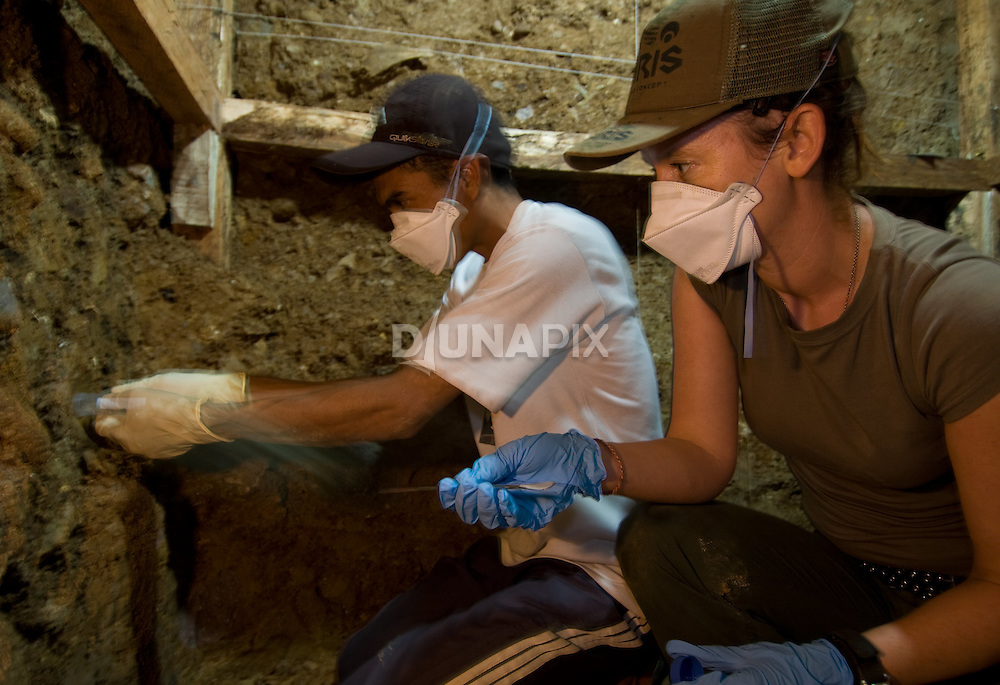 "Kira Westaway and Benjamin Tarus collect samples for dating in an excavation pit at Liang Bua cave, discovery site of the Flores ""hobbit, Homo floresiensis"