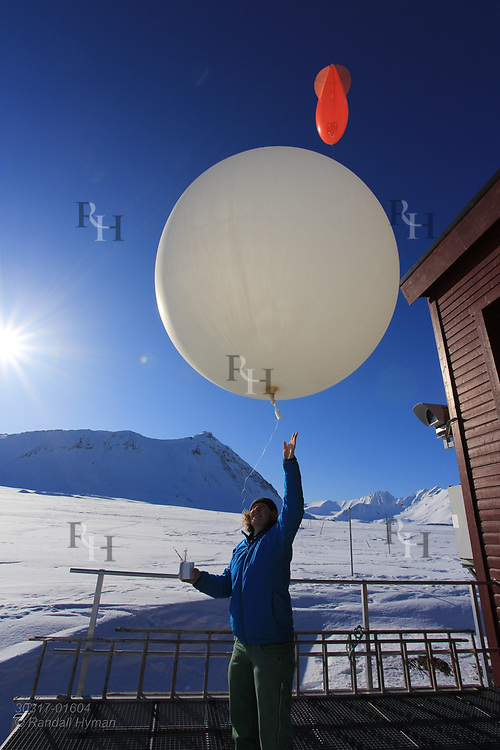 Woman launches weather balloon at the international science village of Ny-Alesund on Spitsbergen island in Kongsfjorden; Svalbard, Norway.