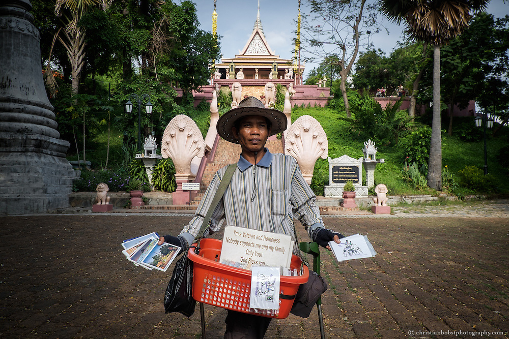 """A one-legged war veteran, waiting at the foot of temple of Wat Phnom to sell postcards to tourists. Wat Phnom is the eponym of Phnom Penh and built on an artificial, 27 meter high hill. The legend says that Stupa of Wat Phnom was built for the wealthy widow of Daun Chi Penh in 1372. She named the temple Wat Phnom Penh. Phnom stands for """"hill"""". Phnom Penh therefore stands for """"hill Penh""""."""