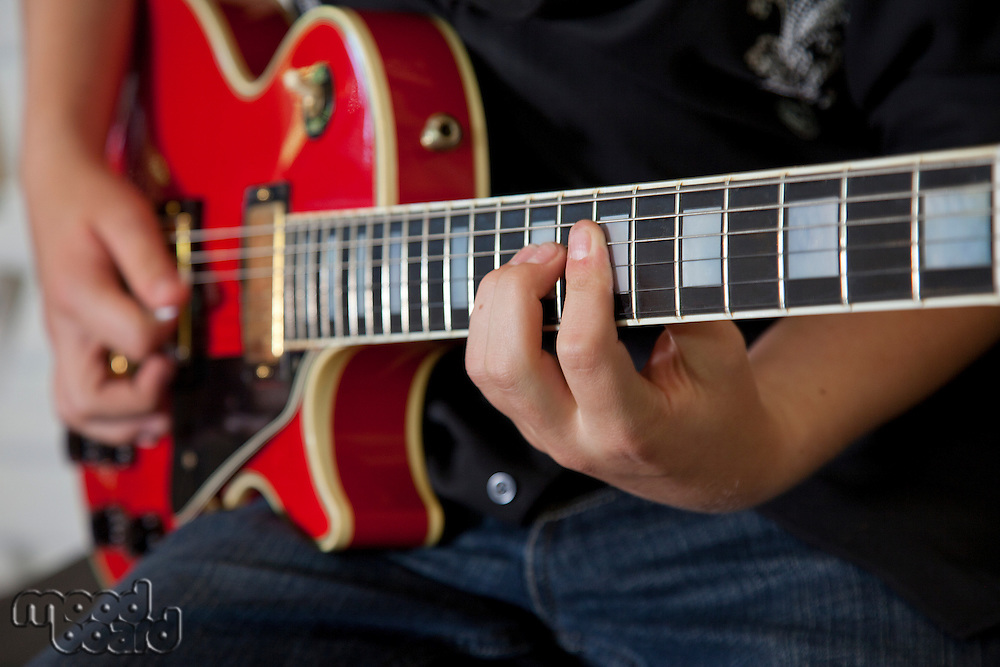 Close-up of young woman's hand playing guitar