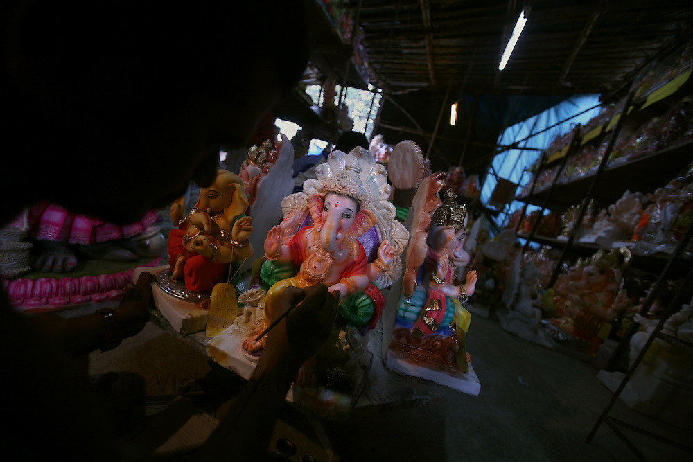 """Skilled labourers work on a unfinished Ganesha Idol in an workshop in Mumbai, September 6, 2007. Lord Ganesha idols are prepared for the """"Ganesh Chaturthi"""" (the Ganesh festival), a popular religious festival in India.Photographer: Prashanth Vishwanathan"""