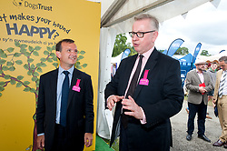 © Licensed to London News Pictures. 24/07/2018. Llanelwedd, Powys, UK. (Visit to Dogs Trust stall) Michael Gove tells a story about his dog - Michael Gove MP, Secretary of State for Environment, Food and Rural Affairs, and Alun Cairns MP, Secretary of State for Wales, visit the Royal Welsh Agricultural Show. The Royal Welsh Agricultural Show is hailed as the largest & most prestigious event of its kind in Europe. In excess of 200,000 visitors are expected this week over the four day show period. The first ever show was at Aberystwyth in 1904 and attracted 442 livestock entries. Photo credit: Graham M. Lawrence/LNP