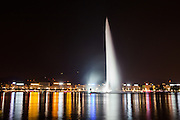 The Jet d'Eau in Lake Geneva shoots water up into the air and splashes back down amongst the reflections of the buildings that line the banks of the lake.