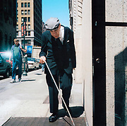 An old blind man walking down the street with his cane, USA