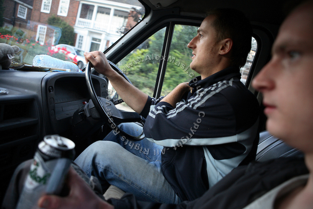 Calin, 30, from Romania, (left) is driving his van along the streets of Hampstead, one of the most exclusive residential areas of London in search of a new mansion to squat. Lukatz, 23, from Poland, (right) is having a beer while checking on the road, in Hampstead, London, England.