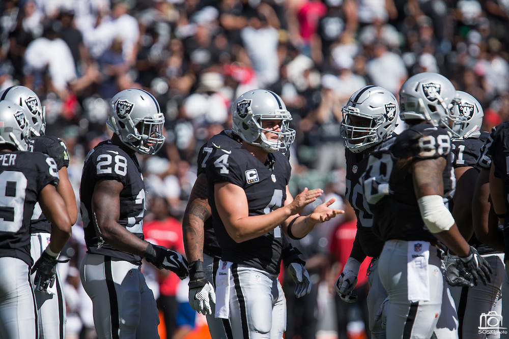Oakland Raiders quarterback Derek Carr (4) calls a play during a huddle against the Atlanta Falcons at Oakland Coliseum in Oakland, Calif., on September 18, 2016. (Stan Olszewski/Special to S.F. Examiner)