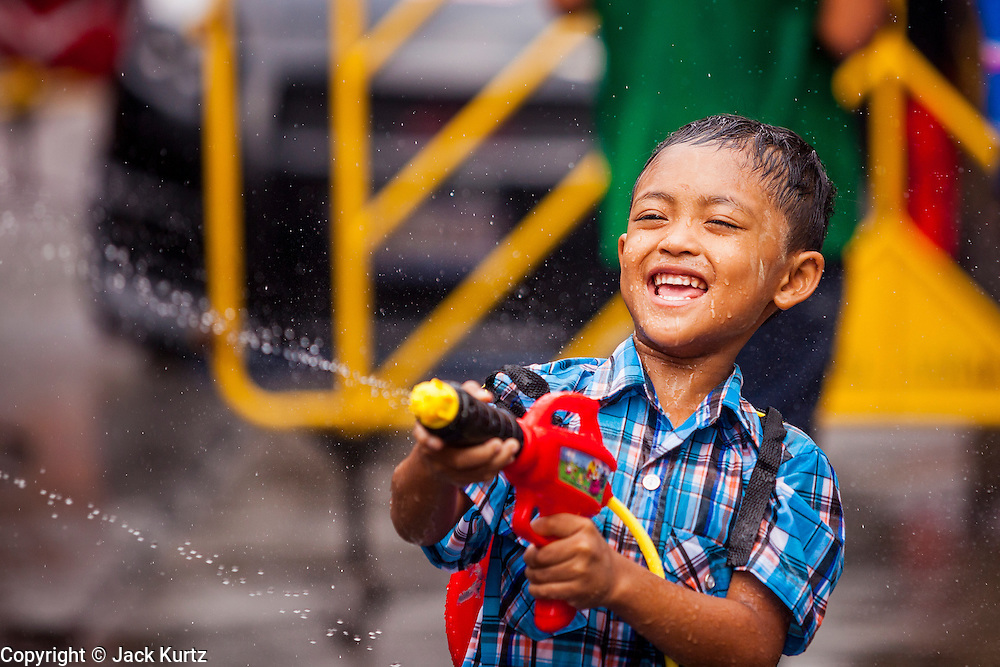 13 APRIL 2014 - BANGKOK, THAILAND: A Thai child with a squirt gun on Khao San Road, Bangkok's backpacker district, during Songkran water fights. Songkran is celebrated in Thailand as the traditional New Year's Day from 13 to 16 April. Songkran is in the hottest time of the year in Thailand, at the end of the dry season and provides an excuse for people to cool off in friendly water fights that take place throughout the country. Songkran has been a national holiday since 1940, when Thailand moved the first day of the year to January 1.    PHOTO BY JACK KURTZ