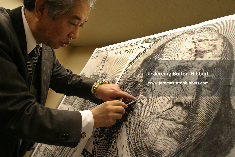 """Yoshihide Matsumura, Director of Matsumura Technology Co. Ltd, a Japanese company specializing in machines to detect counterfeit currencies, detecting discrepancies on a fake dollar note bearing the face of President Benjamin Franklin. Photographed with fake American dollar bank notes, Euros, and Japanese Yen. His 'Matsumura 4 + 1' counterfeit currency detection machine retails for 4,500 USD, and can detect the best fake notes such as the American dollars """"Super K"""", and """"Super Z"""" fakes."""