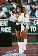 A Los Angeles Raiders cheerleader performs during the NFL football game between the Denver Broncos and the Los Angeles Raiders on December 4, 1988 in Los Angeles, California. The Raiders won the game 21-20. ©Paul Anthony Spinelli