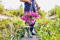 Portrait of mature male gardener holding flower in shop