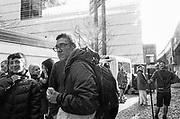 Man eating apple outside Hidden Club in Vauxhall, London, UK,  February 2015