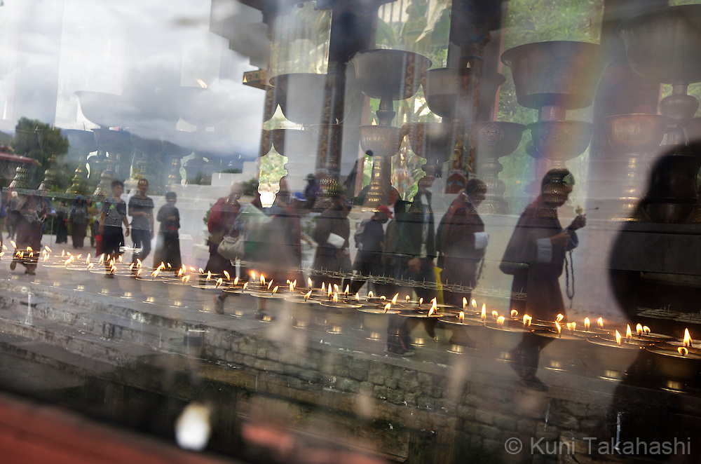 Worshippers are seen reflected on the window of the room for butter lamps at the National Memorial Chorten (religious monument) in Thimpu, Bhutan on August 12, 2014. The Tibetan-style chorten, built in 1974 as a memorial to the third king, Jigme Dorji Wangchuck (1928–72), is the focus of daily worship among buddhists in Thimpu. (Photo by Kuni Takahashi)