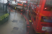 Aerial view through misted bus window of red buses below during seasonal downpour of rain.